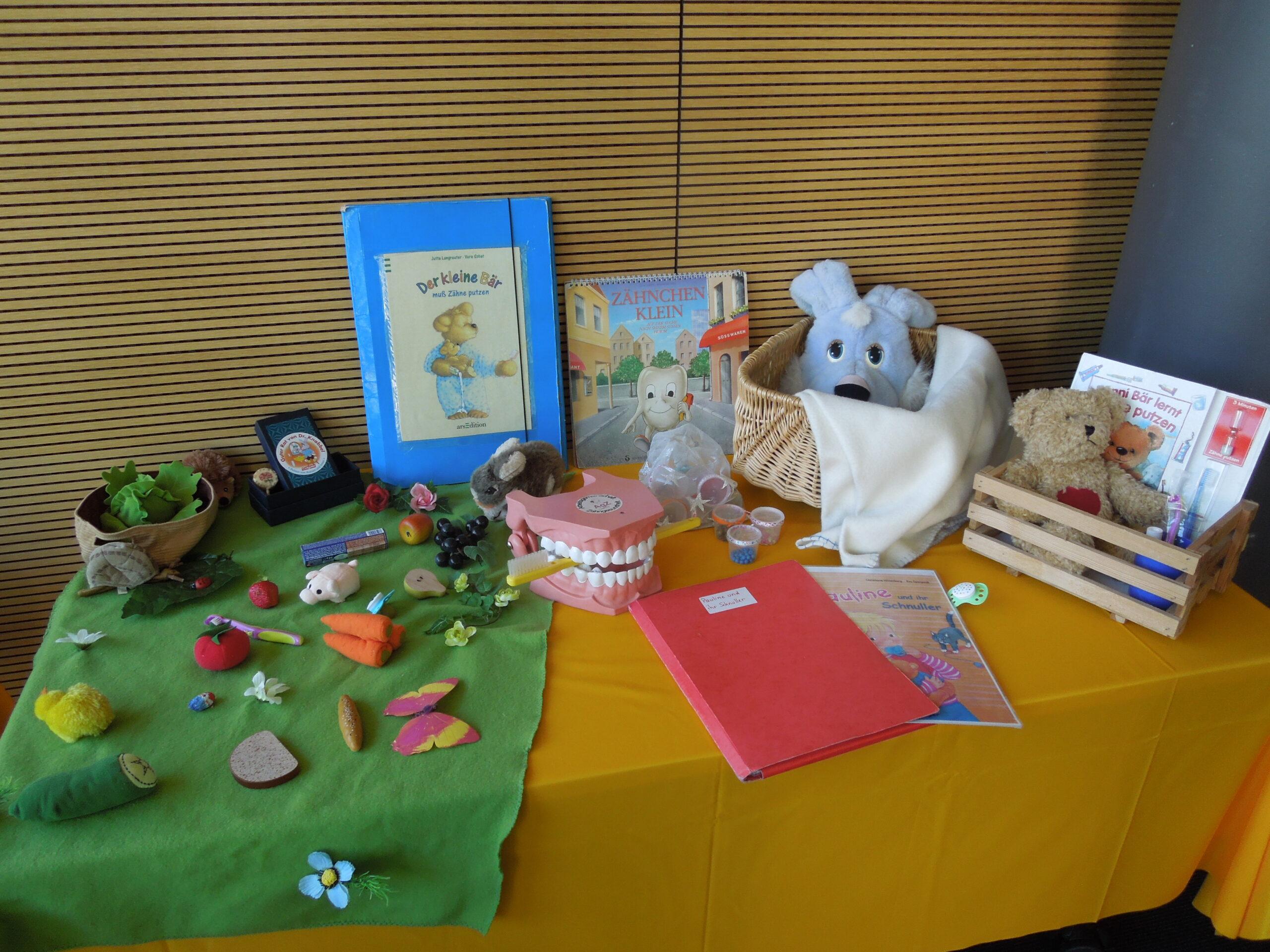 Tisch mit verschiedenen Arbeitsmaterialien, grüner Teppich mit Spielobst , Bücher, Großes Gebiss und Kuscheltiere