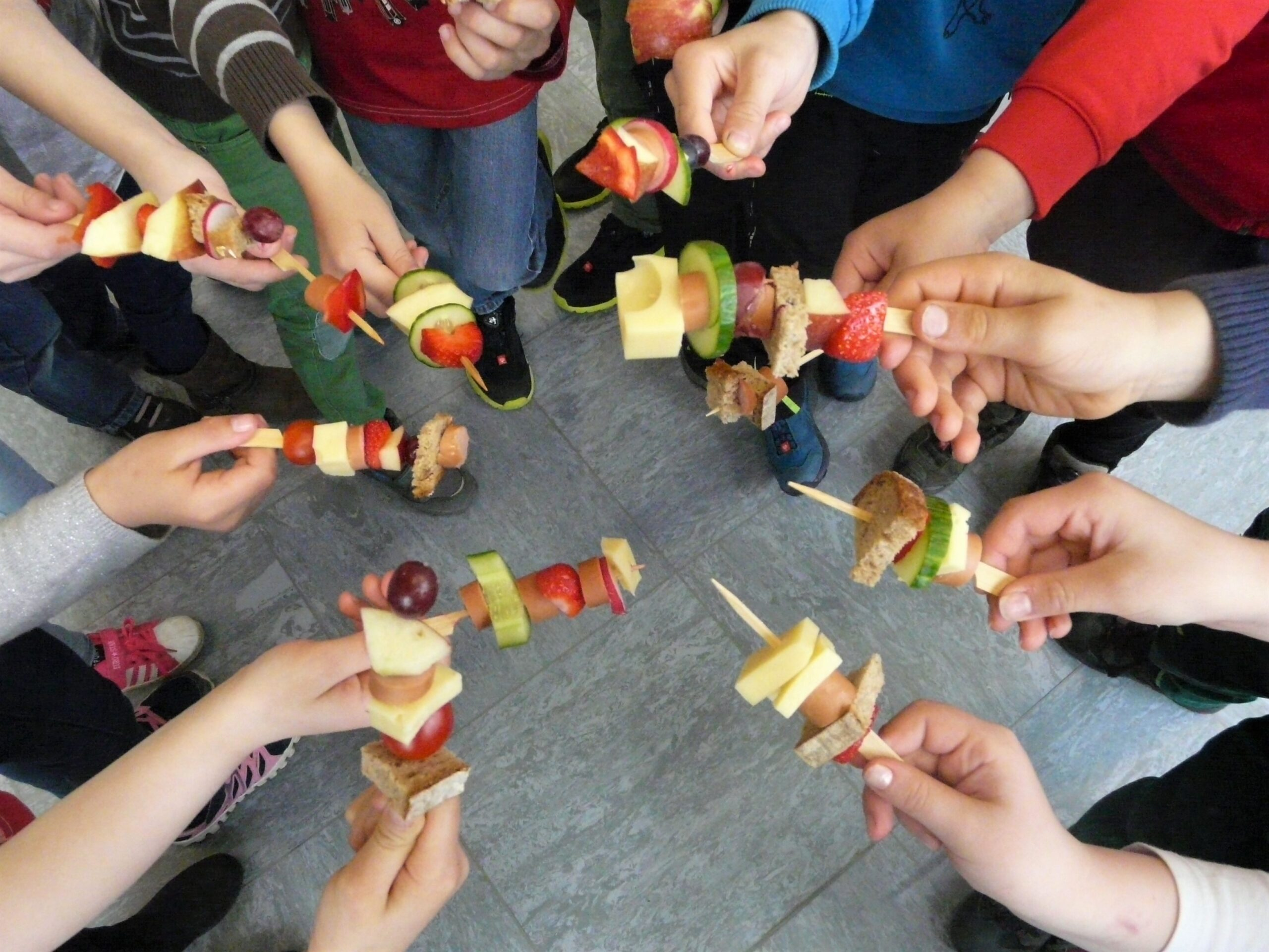 Gesundes Schulfrühstück- Kinder zeigen ihre selbstgemachten Spieße mit Obst, Gemüse, Brot, Käse und Wurst
